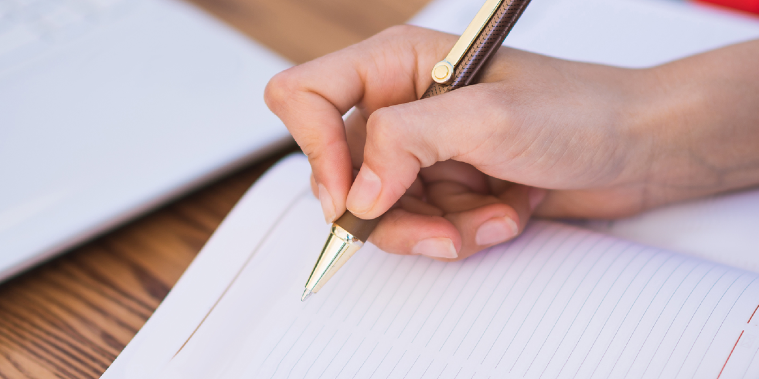 Person holding a pen about to write on some paper